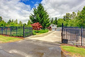 House exterior with open iron gate driveway and garage